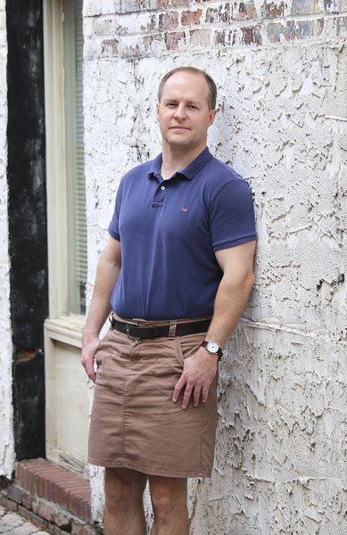 Muscular man in masculine brown skirt and blue polo shirt